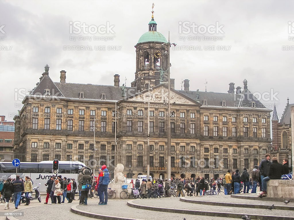People on  Dam Square in front of  Amsterdam Royal Palace stock photo