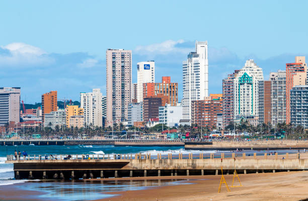 People on Early Morning Beach Against City Skyline – Foto