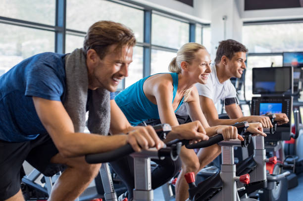people on exercise bike - health club stock photos and pictures