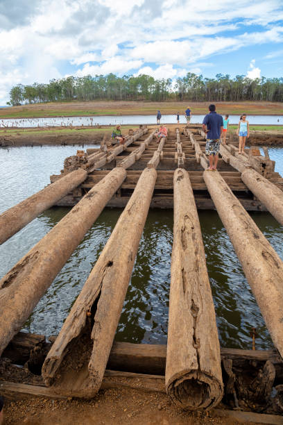 People on exposed old bridge in drought affected Lake Tinaroo on the Atherton Tablelands in Tropical North Queensland, Australia stock photo