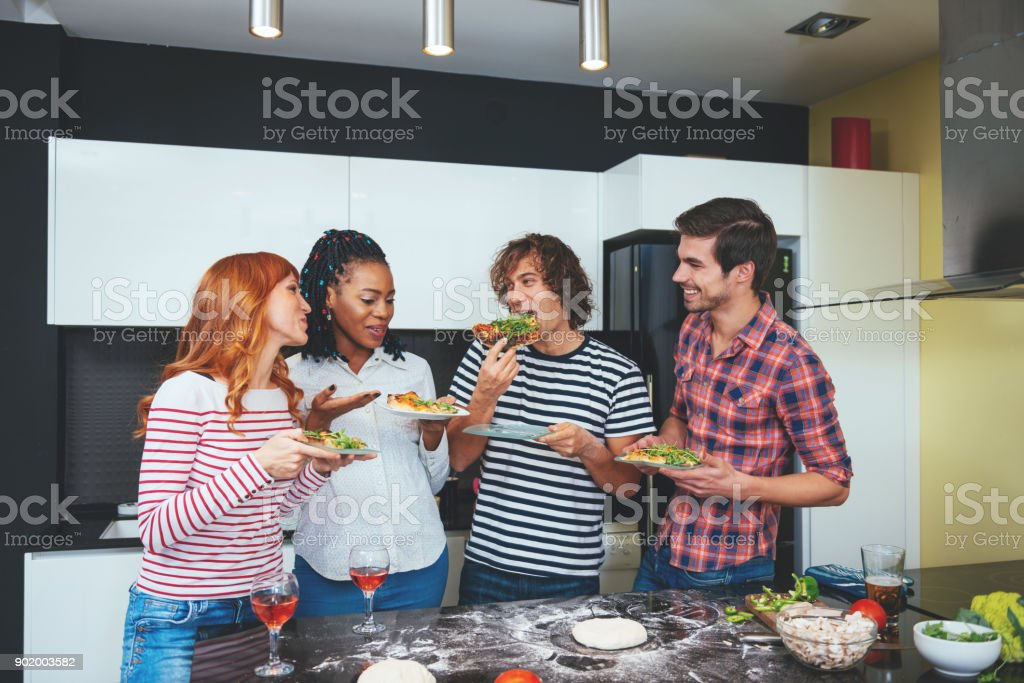 People on house party eating pizza slices in kitchen stock photo