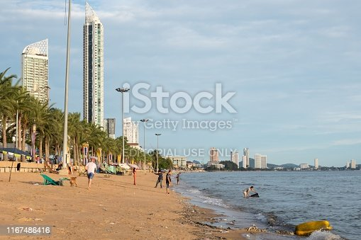 People enjoy themselves at the smaller Jomtien beach in Pattaya, Thailand. Some trash can be seen where the sea meets the land.