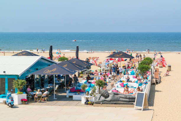 People on lounge terrace of waterfront beach club in Scheveningen, The Hague, Netherlands People enjoying and relaxing on lounge terrace of waterfront beach club in Scheveningen, The Hague, Netherlands pavilion stock pictures, royalty-free photos & images