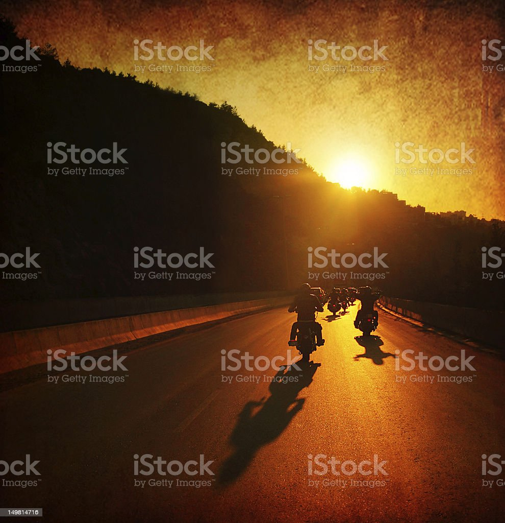A large group of motorcycles are riding into the summer sunset. The...