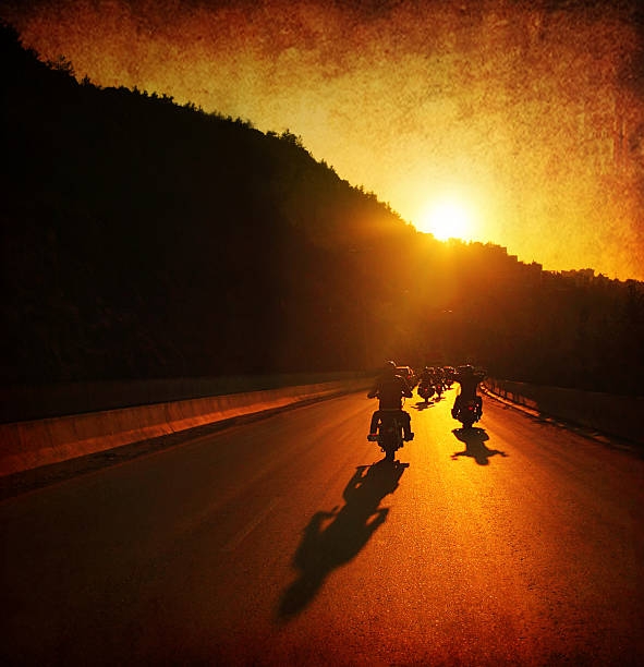 people on motorcycles at sunset - biker stock photos and pictures
