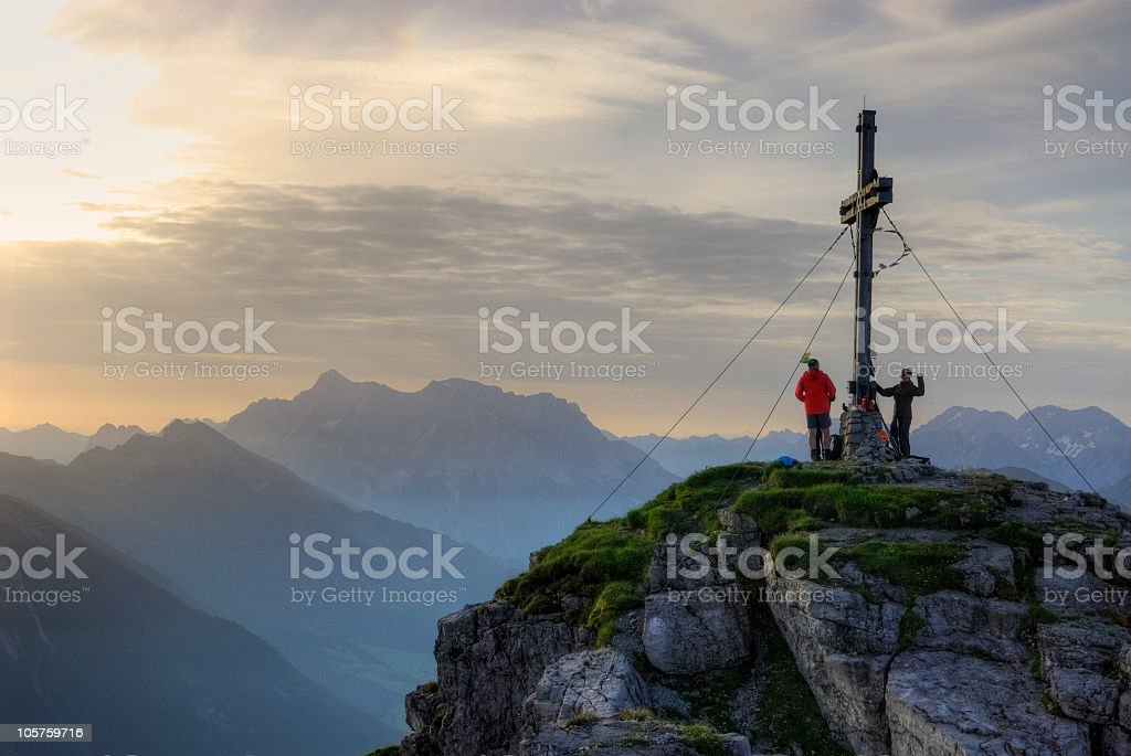 People on mountain peak near the cross with warm sun stock photo