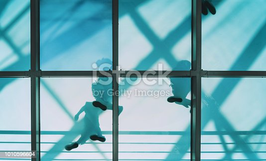 low angle view on people going on transparent glass bridge