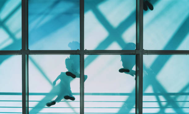 people on pedestrian glass bridge low angle view on people going on transparent glass bridge man made structure stock pictures, royalty-free photos & images