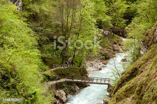 View from above of people trekking on pedestrian path and wood bridge over Tolminka river in Tolmin Gorges