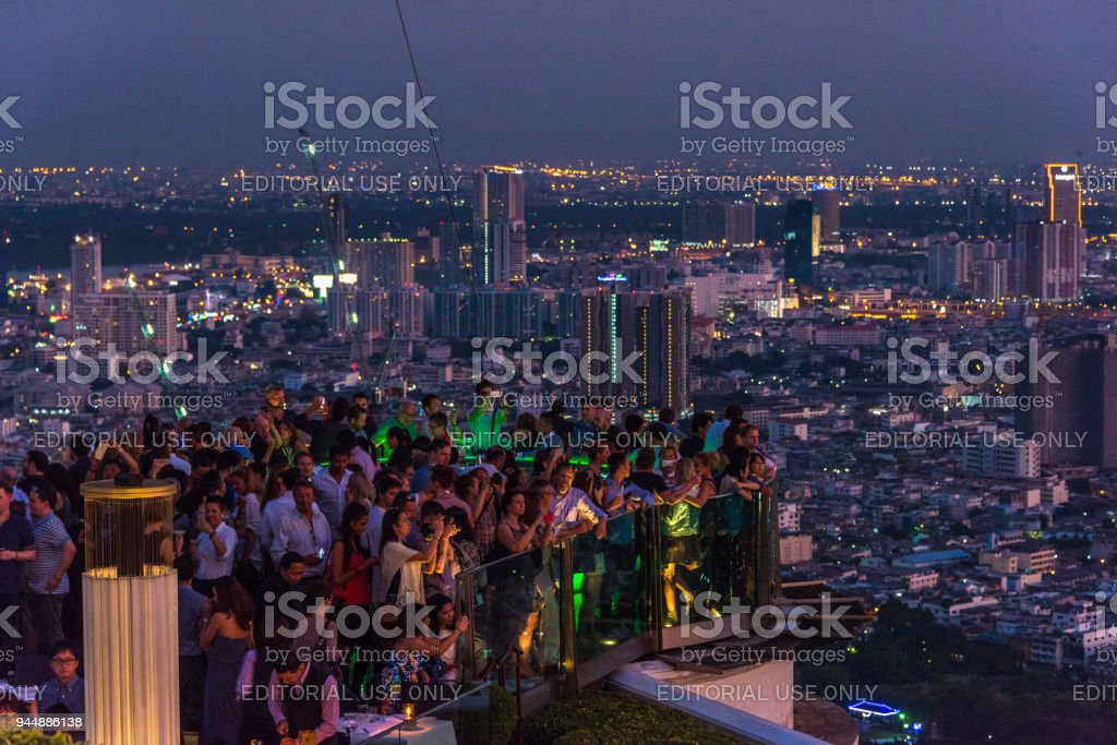 People on rooftop bar with Bangkok cityscape stock photo