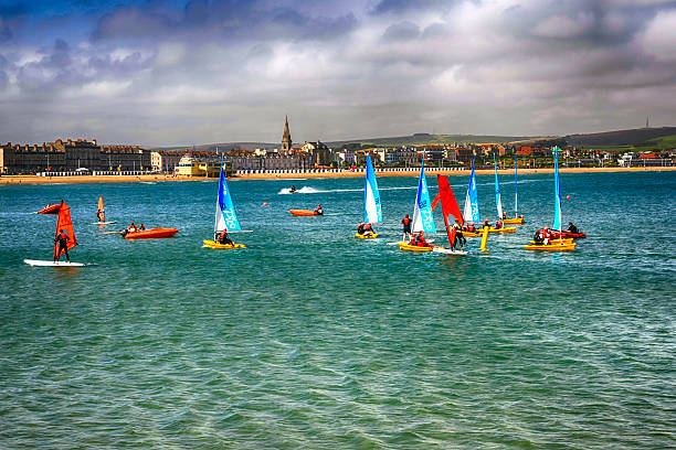 people on sailboards and in sailboats in weymouth bay, uk - weymouth stock photos and pictures