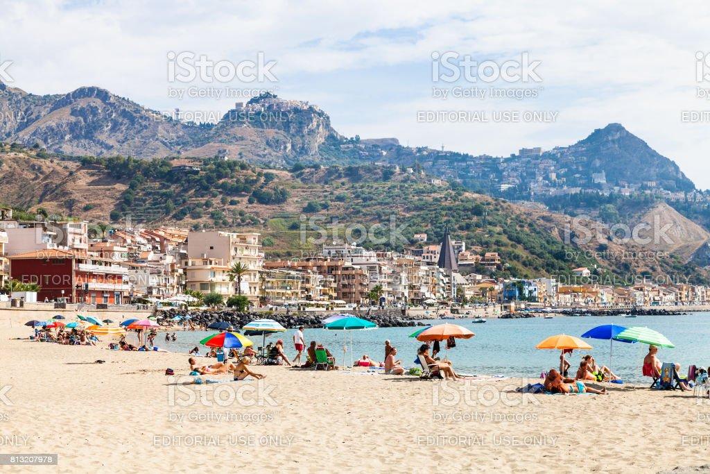 people on sand beach in Giardini Naxos town stock photo