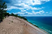 Sleeping Bear Dunes National Lakeshore, MI, USA - August 9, 2011: People Walking on Sand Dune on Coast of Lake Michigan on Beautiful Summer Day with Dynamic Clouds in Blue Sky