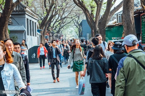 Beijing China - April 18, 2018: People visit Nanluoguxiang futong street in Beijing China. Nanluoguxiang lane has become a popular tourist destination with restaurants and bars. The street is lined with retail shops, boutique fashion stores, souvenir shops, restaurants and eateries.