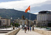 Skopje, Republic of Macedonia - September 6, 2015: People on stone bridge and the view of bronze statue of Alexander the Great on a rearing horse holding a sword high up in Skopje city main square, Former Yugoslav Republic of Macedonia (Macedonia FYR). Monument of Alexander the Great in Skopje central square, Republic of Macedonia. Giant bronze statue of Alexander the Great is 12 meters high. The official name is \
