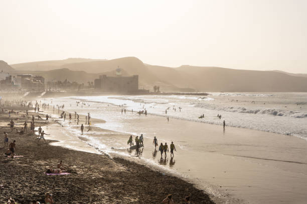 """People on the beach during sand storm from Africa known as """"Calima"""" at Las Canteras beach in Las Palmas with the Alfredo Kraus Auditorium in the background stock photo"""