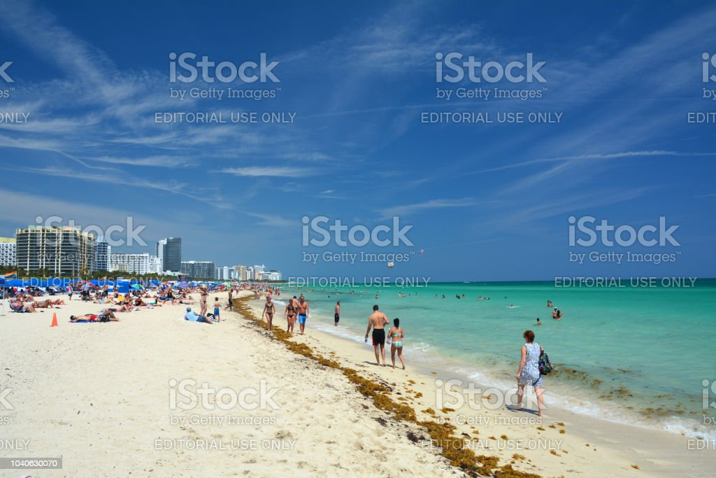 People on the beach in Miami Beach MIAMI BEACH, USA - APRIL 1, 2017 : People enjoy perfect weather on the beach in South Beach. Atlantic Ocean Stock Photo