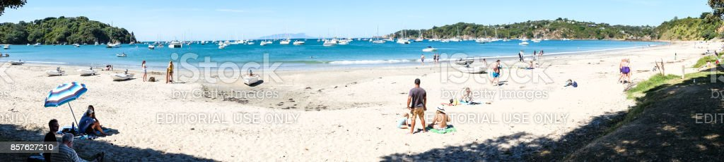 People on the beach plus a busy anchorage with many boats stock photo