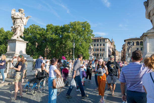 people on the bridge of the holy angel in rome - rome road central view foto e immagini stock