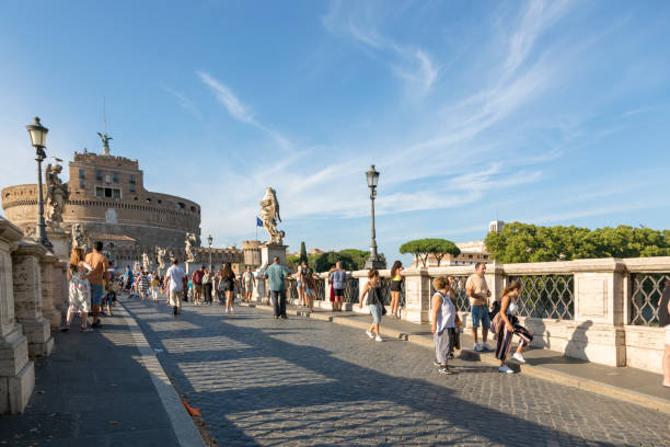 people on the bridge of the holy angel on the background of the castle of the holy angel in rome - rome road central view foto e immagini stock