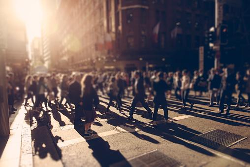Crowd of people walking over the crosswalk at sunset. Sydney, Australia