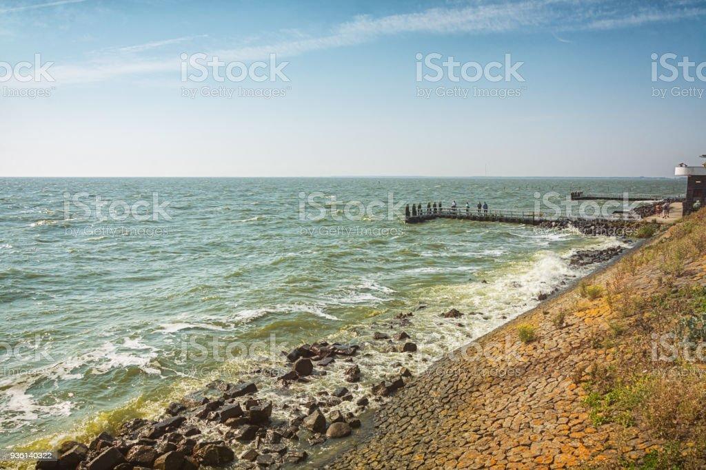Mensen op de pier langs de Afsluitdijk in het IJsselmeer foto