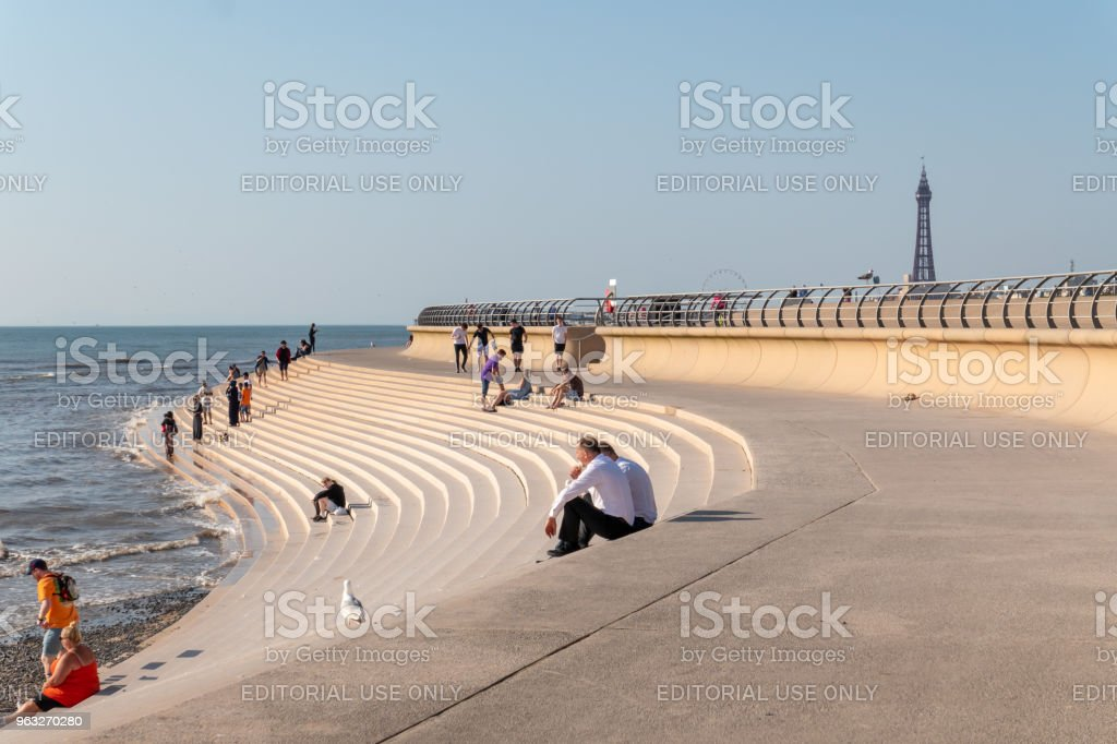 People on the steps by the sea in Blackpool stock photo
