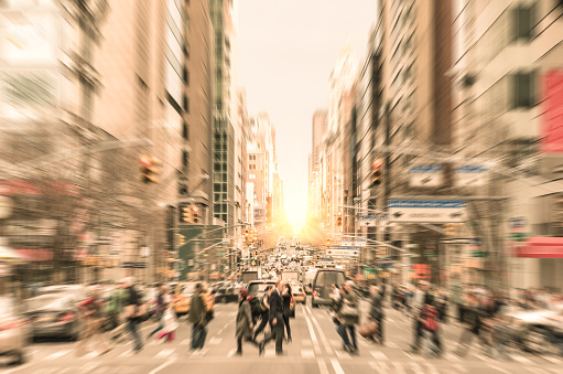 People on the street on Madison Avenue in Manhattan downtown before sunset in New York city - Commuters walking on zebra crossing during rush hour in american business district - Radial defocusing added during editing to make all the people completely unrecognizable