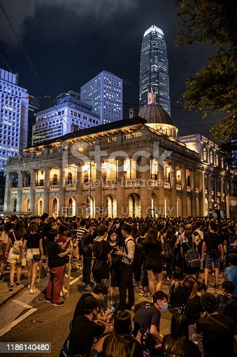 Hong Kong - August 28, 2019: People dressed in black, the color of protest, stand on a street adjacent to Chater Garden in Hong Kong's Central District. The illuminated facade of the neoclassical Court of Final Appeal is in the background.