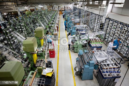 Latin American people operating machines at a textile factory - industrial concepts