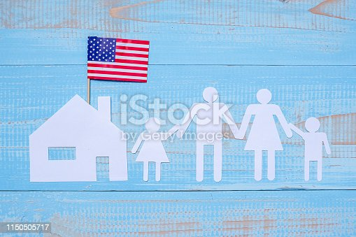 istock People or Family and home paper shape with  flag of the United States of America on blue wooden background. USA holiday of Veterans, Memorial, Independence and Labor Day 1150505717