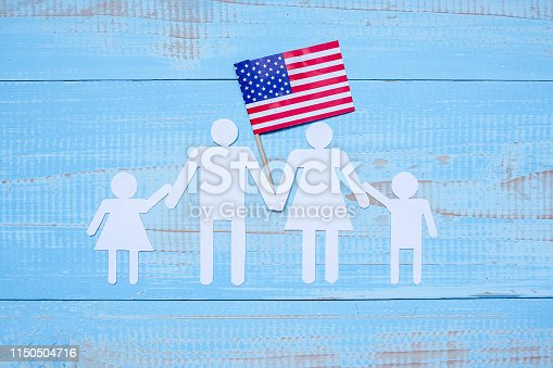 istock People or Family paper shape with  flag of the United States of America on blue wooden background. USA holiday of Veterans, Memorial, Independence and Labor Day 1150504716