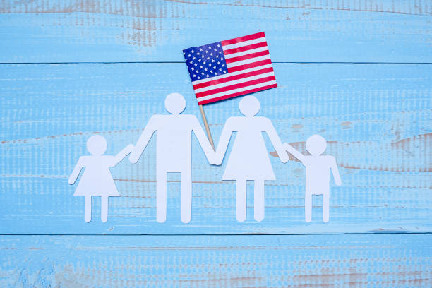 people or family paper shape with  flag of the united states of america on blue wooden background. usa holiday of veterans, memorial, independence and labor day - fourth of july стоковые фото и изображения