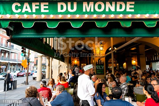 istock People ordering food in Cafe Du Monde restaurant, eating beignet powdered sugar donuts, drinking chicory coffee, waiter taking order 1175113525
