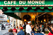 New Orleans, USA - April 22, 2018: People ordering food in Cafe Du Monde restaurant, eating beignet powdered sugar donuts, drinking chicory coffee, waiter taking order