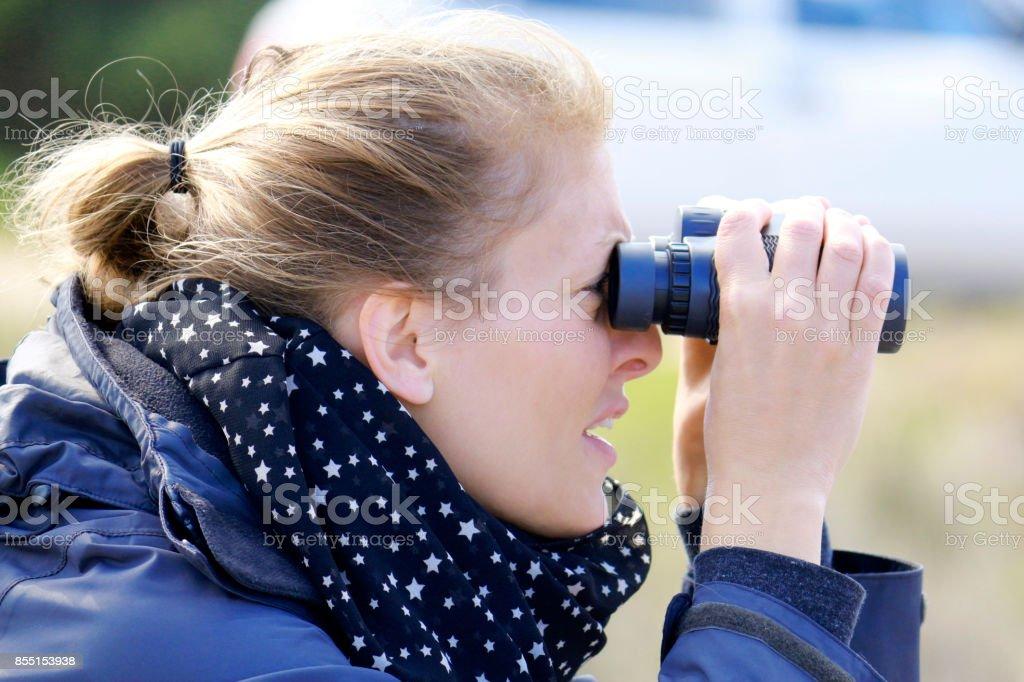 Einzelne junge ornithologen frau mit fernglas für