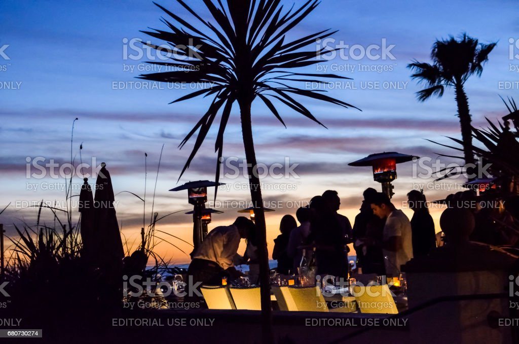 People outside in famous Hotel del Coronado bar and restaurant at night in California with sunset and illuminated objects stock photo