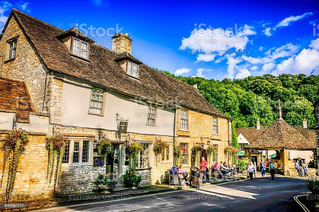People outside the pub in Castle Combe, UK stock photo