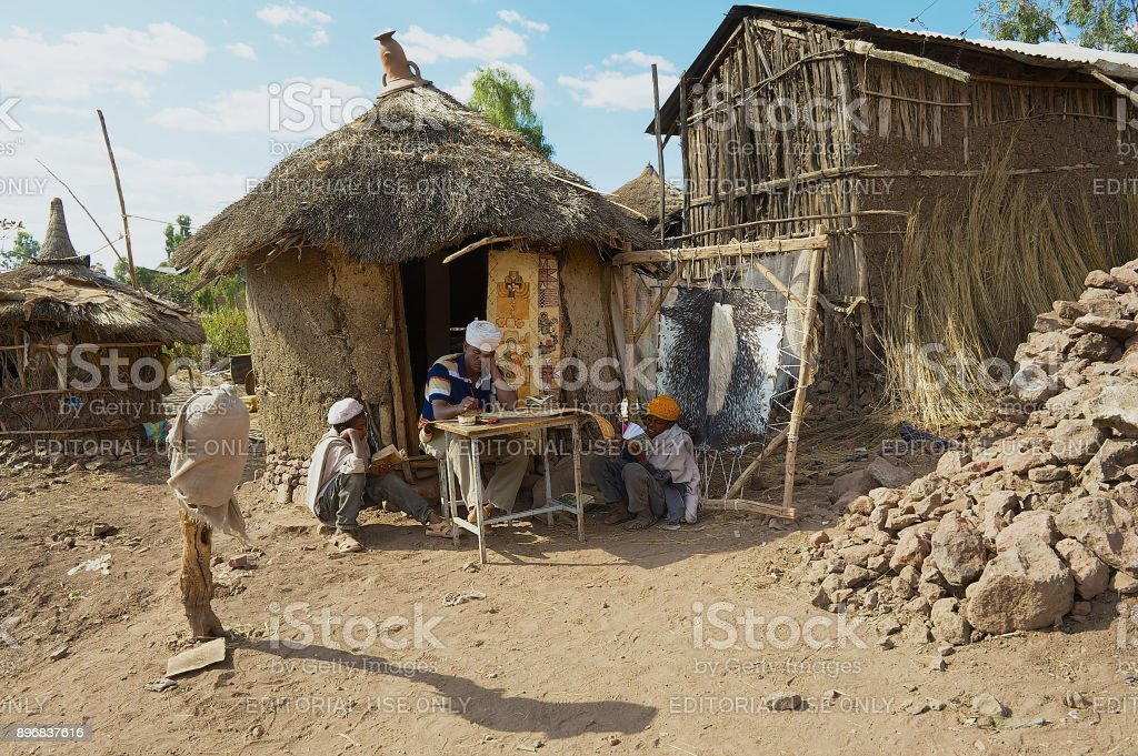 People paint and read at the house entrance in Lalibela, Ethiopia. stock photo