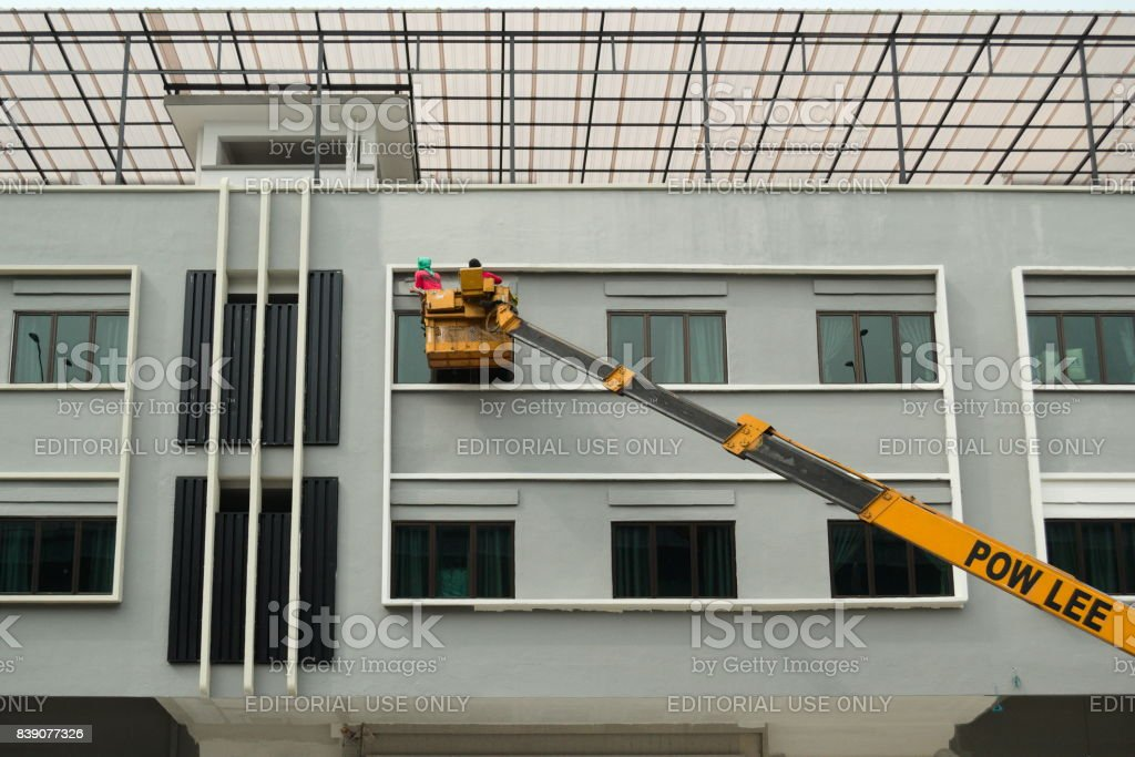 People paints a building on a yellow crane stock photo