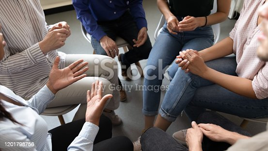 Top close up view in circle sit people, corporate teambuilding activity solve issues talk think together or alcohol rehab addiction treatment, twelve-step program, physical, mental, spiritual concept