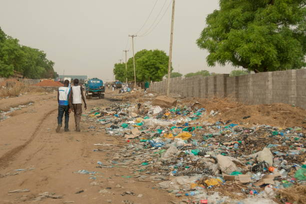 People pass by rubbish dump on a street in Juba, South Sudan. stock photo