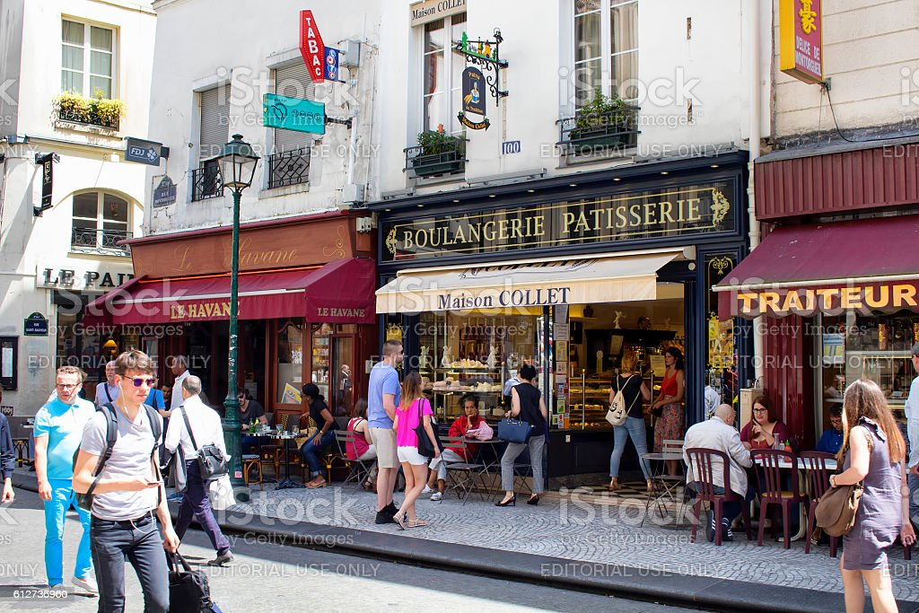 People passes by a cafe on Rue Montorgueil street. stock photo