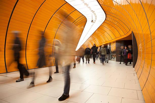 pendler gegen modernen orange hintergrund - arbeit in münchen stock-fotos und bilder
