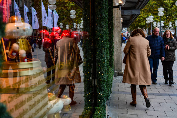 People passing by showcase of the famous Oberpollinger mall at Neuhauser street stock photo