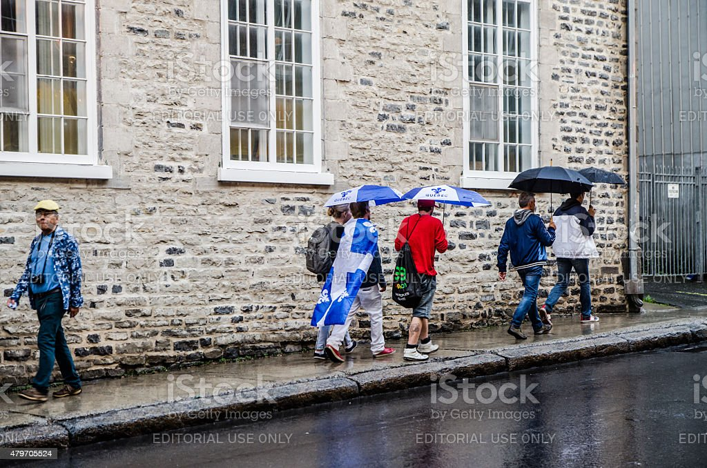 People passing by wearing Flag province of Quebec stock photo