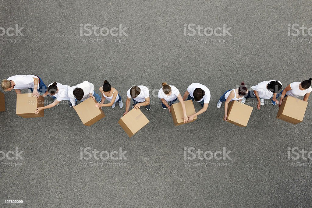 People passing cardboard boxes stock photo
