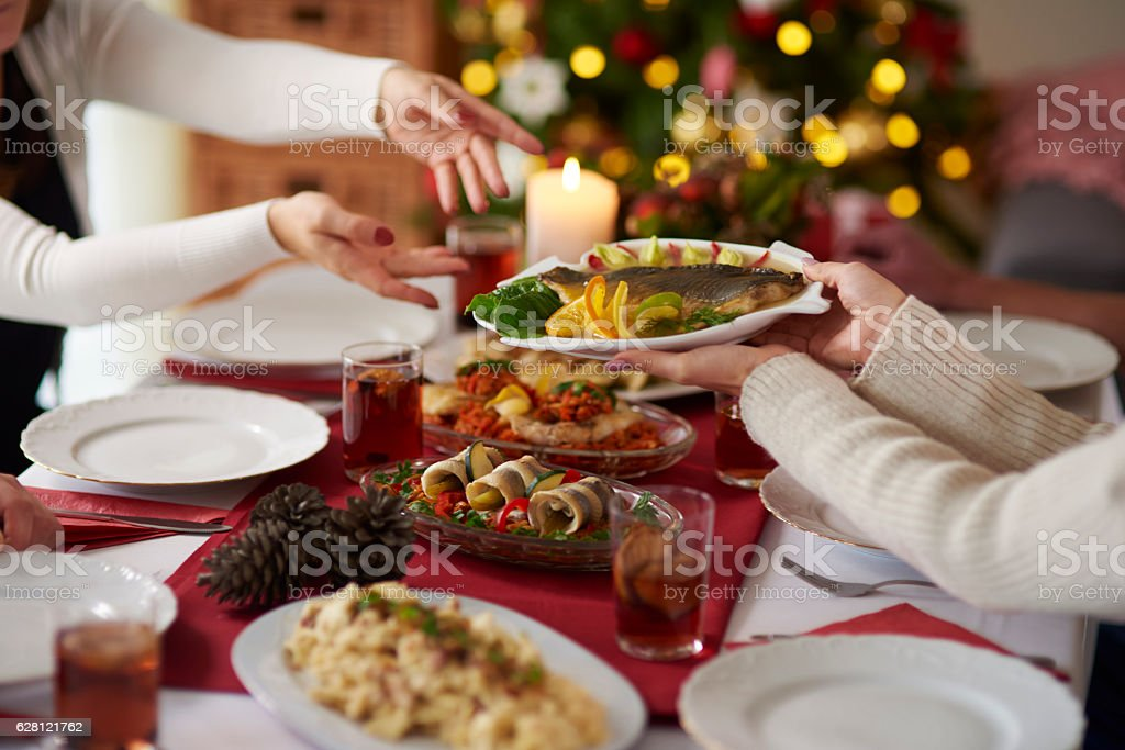 People passing plate with Christmas carp stock photo