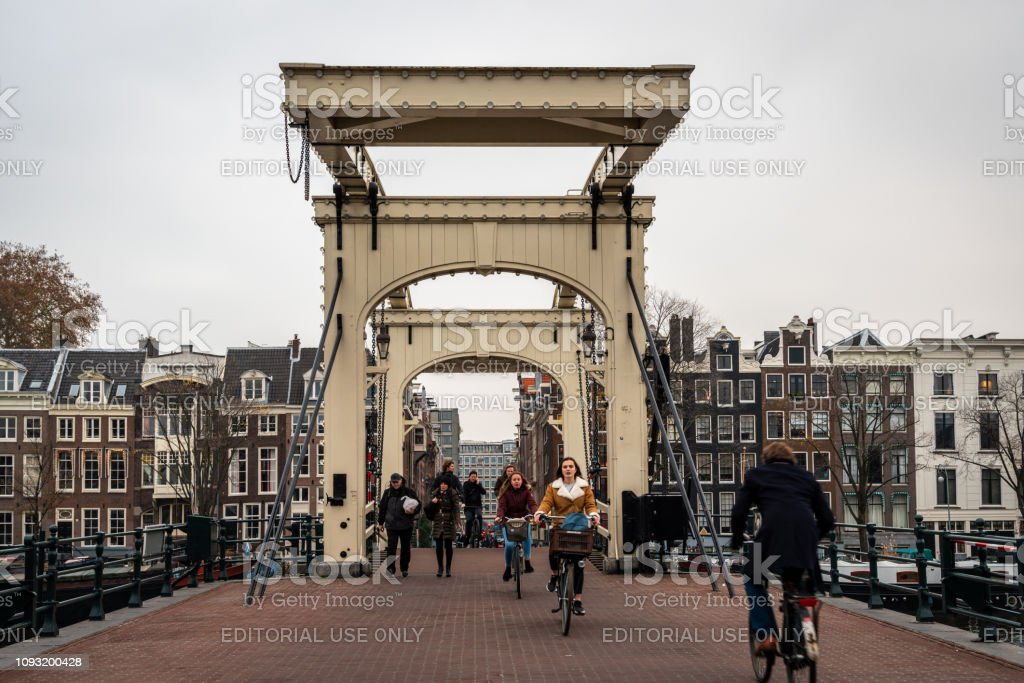 People passing the famous wooden drawbridge Magere Brug in Amsterdam. stock photo