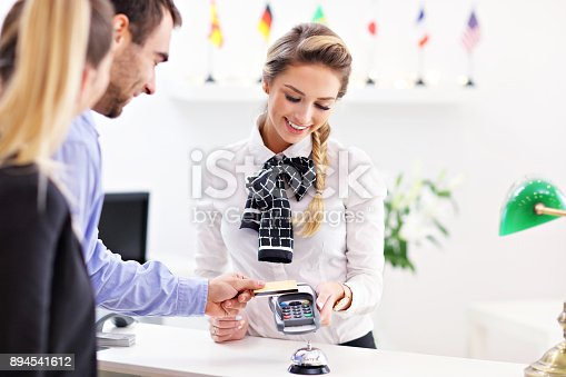 istock People paying in hotel reception 894541612